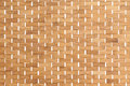 Background texture of a bamboo mat woven or rattan with natural fibre detail and white stitching Royalty Free Stock Photo