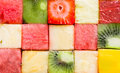 Background texture of diced tropical summer fruit cut in cubes and arranged in rows for a seamless pattern with watermelon Royalty Free Stock Photo