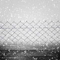 Background winter fence wooden panel wire grey with a falling snow Stock Photo