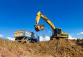 Backhoe digging and trucks bottom view ponds to pour into the truck looking through the blue sky Stock Photography