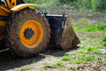 Backhoe loader front detail wheel and of a parked on the dirt ground with grass Royalty Free Stock Photos