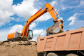 Backhoe loading soil into dump truck body Stock Photo
