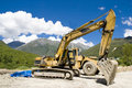 Backhoe working against a mountain landscape Stock Photography