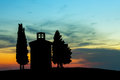 Backlit chapel in tuscany with cypress trees near pienza Stock Photos
