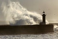 Backlit dramatic wave big over lighthouse Stock Photos