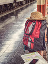 Backpack, hat, cellphone and map on bench at the station. Royalty Free Stock Photo