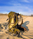 Backpack on sandy road Stock Images