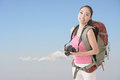 Backpacker with camera happy smiling asian young female standing in front of blue sky Stock Images