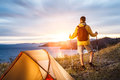 Backpacker in a camp looking at beautiful sunrise at big lake near tent Royalty Free Stock Image