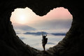 Backpacker in cave enjoy mountain view silhouette of female with bag standing inside shaped heart symbol while enjoying Stock Images
