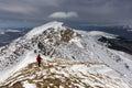 Backpacker climbing a mountain snowy ridge winter Royalty Free Stock Photo