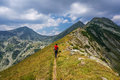 Backpacker hiking in the mountains on a tourist track with backpack walking mountain Royalty Free Stock Photography
