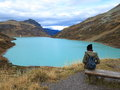 Mountain lake landscape with woman on bench Royalty Free Stock Photo