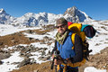 Backpacker mountaineer man portrait standing rest snow mountain.