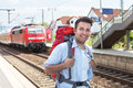 Backpacker at railway station with train Royalty Free Stock Photo