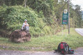 Backpacker waiting for hitchhike on the road for kubah national park west sarawak borneo malaysia people traveling lifestyle Stock Photos