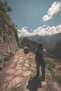 Backpacker walking on the Inca Trail above Machu Picchu, the most visited travel destination in Peru. Rear view, toned Royalty Free Stock Photo