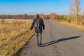 Backpacker walking on a road in Ukrainian rural area at fall season Royalty Free Stock Photo