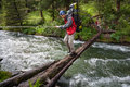 Backpackers are crossing mountain river Royalty Free Stock Photo