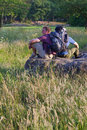 Backpackers in sunny field Stock Photo