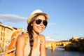 Backpacking women traveler in florence woman on travel wearing sunglasses smiling happy by ponte vecchio during vacation holidays Royalty Free Stock Image