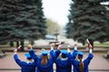 Backs of graduates ecstatic students in graduation gowns holding diplomas Stock Image