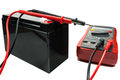 Backup battery with a multimeter and probes on a white background Royalty Free Stock Photo