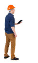 Backview of business man in construction helmet stands and enjoy enjoys tablet or using a mobile phone standing young guy rear Royalty Free Stock Images