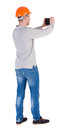 Backview of an engineer in construction helmet stands and enjoys tablet or using a mobile phone standing young guy rear view Royalty Free Stock Photography