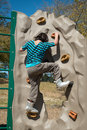 Backview of grade school age girl climbing rock climbing wall outdoors in the park Royalty Free Stock Photos
