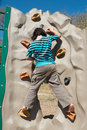 Backview of grade school age girl climbing rock climbing wall outdoors in the park Royalty Free Stock Photo