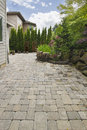 Backyard brick paver patio with pond garden hardscape pavers trees natural rocks landscaping Royalty Free Stock Image