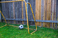 Backyard chldren soccer at the wood fence with wall goal leather ball on grass Stock Images