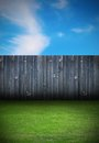 Backyard with old wooden fence backdrop of black and green grass Royalty Free Stock Photography