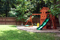 Backyard playground with wooden trees and grass Stock Image