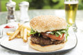 Bacon and bleu stuffed cheeseburger topped with arugula tomato on a toatsed sesame seed bun served with fries ketchup beer Stock Image