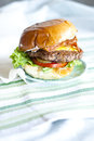 Bacon cheeseburger freshly made on porcelain plate set on cloth covered table Royalty Free Stock Photo