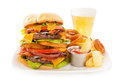 Bacon double cheeseburger with fries and onion rings a very tall hamburger stacked two beef patties crisp cheddar cheese blue Stock Image