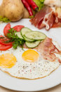 Bacon and eggs with garnish on white plate hot Royalty Free Stock Photo