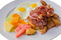 Bacon ham potato fruit egg breakfast an isolated plate of hams potatoes fruits and eggs Stock Photo
