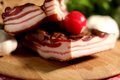 Bacon with onion and charry tomato on wooden board Royalty Free Stock Image