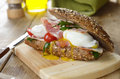 Bacon and poached eggs sandwich on the cut board Stock Photography