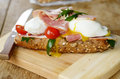 Bacon and poached eggs sandwich on the cut board Royalty Free Stock Photos