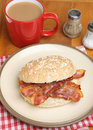 Bacon roll tea crispy in a wholemeal with a mug of Stock Photography