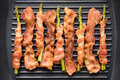 Bacon slice and asparagus wrapped in bacon being cooked in fryin Royalty Free Stock Photo