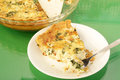 Bacon and spinach quiche slice of on white plate with pie plate in background reflecting in green glass top table Stock Photo