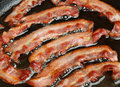 Bacon strips cooking in frying pan rashers being cooked Royalty Free Stock Images