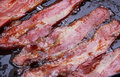 Bacon strips or rashers being cooked in frying pan Stock Photo
