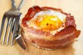 Bacon wrapped egg oven cooked with fork and knife Royalty Free Stock Images
