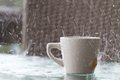 Bad day for having a drink outside in the downpour of rain heavy storm on table with coffee mu with tea Stock Photo